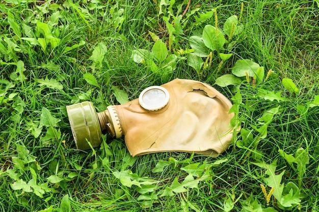 На зеленой траве лежит старый противогаз. концепция защиты окружающей среды