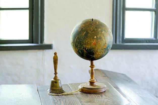 背景の教室に対してテーブルの上に横たわっている古い地球儀。レトロなスタイル。科学、教育、旅行、ヴィンテージの背景。教育の歴史と地理のチーム。