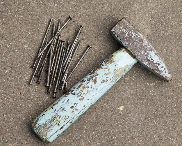 古いハンマーと釘がアスファルトの上にあり、作業用の作業工具です。上面図。フラットレイ