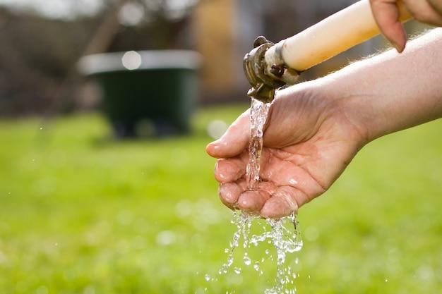 Старая рука активного пожилого человека моет грязную руку после садовых работ в своем огромном ботаническом саду