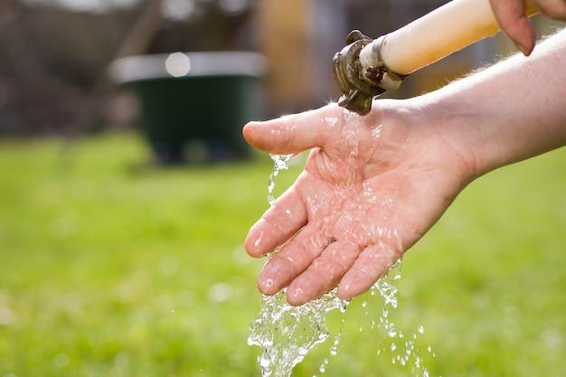 彼の巨大な植物園で庭仕事をした後、彼の汚れた手を洗うアクティブな先輩の古い手