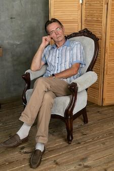 안락의자에서 쉬고 있는 지적인 노인