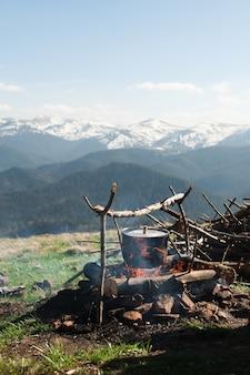 오래된 작은 보일러가 녹색 산 초원에서 불에 가열됩니다.