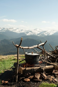 오래된 작은 보일러가 녹색 산에서 불에 가열됩니다.