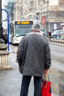 Старик в куртке и шляпе из шерсти на остановке, улица на заднем плане, пасмурная погода в бухаресте, румыния