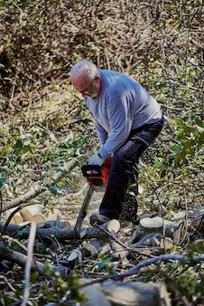 Старик вырубает упавшее дерево в лесу.