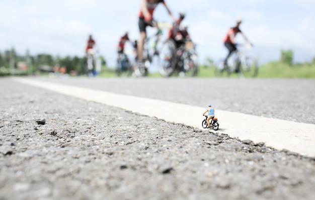 Миниатюрный старик на велосипедной прогулке по проселочной дороге на фоне группы велосипедных гонок
