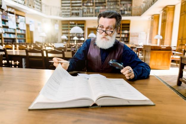 古代の図書館のテーブルに座って本を読んでいるスタイリッシュなカジュアルなヴィンテージの服を着た老人教師の教授。教育、図書館のコンセプト