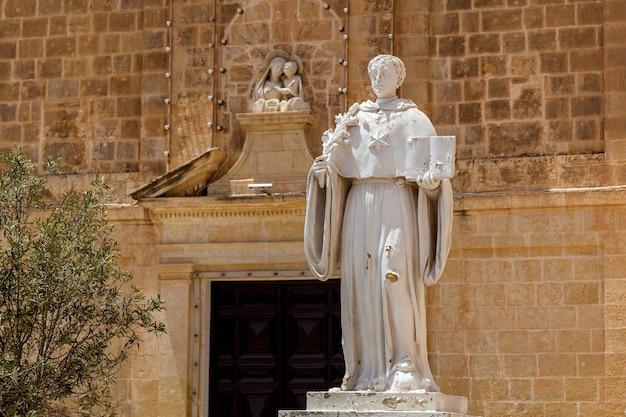 Старинная средневековая скульптура с фигурой святого в полный рост с маленьким ребенком на фасаде