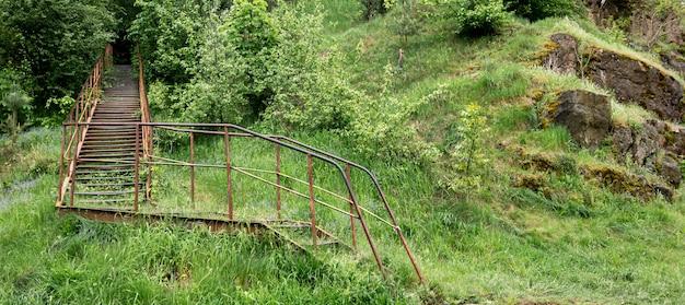 산 사이 숲으로 이어지는 오래된 금속 계단