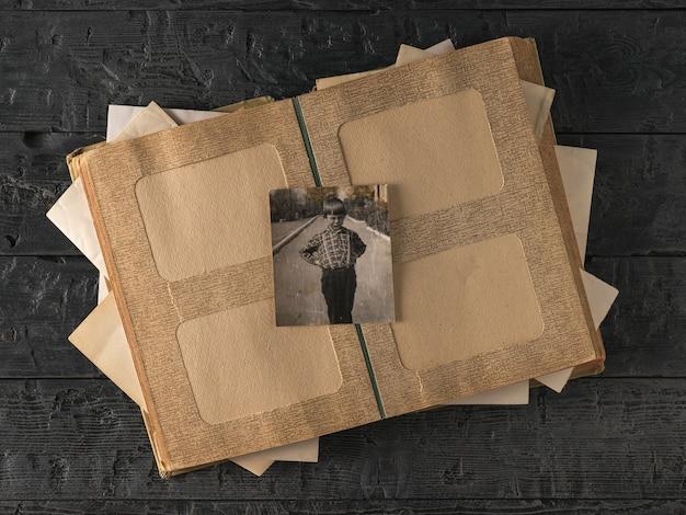 Старая фотография ребенка над открытым фотоальбомом. стильное старое фото. история.