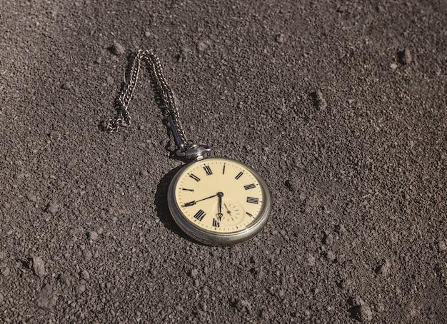 오래된 회중 시계가 마른 땅에 놓여 있습니다. 과거와 미래 시제.