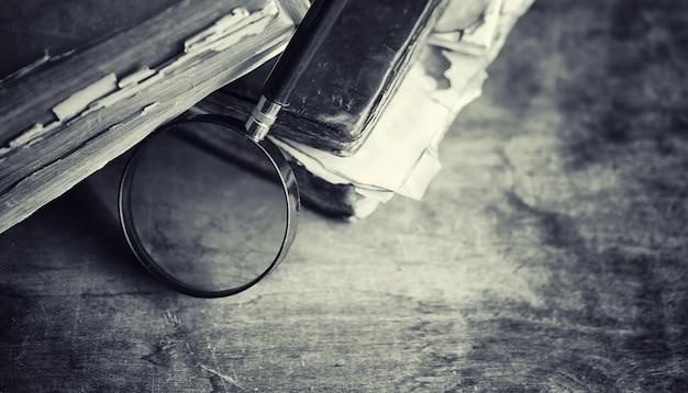 テーブルの上の古いレトロな本。古い木製のカウンタートップにある過去の百科事典。バイバイオティクス、フォリオ、憲法、聖書からの古い本。