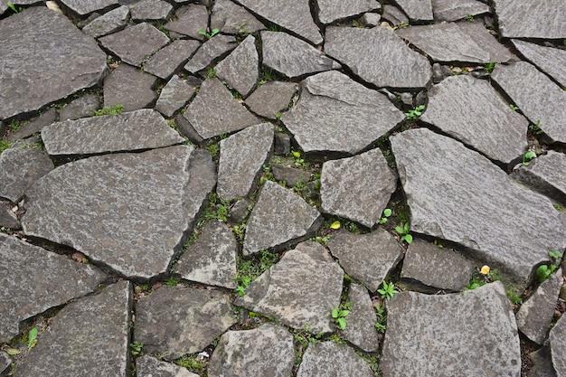 Старая дорога или тротуар, выложенный неровными камнями разного цвета и формы. между камнями растет трава. сфотографирован полный кадр