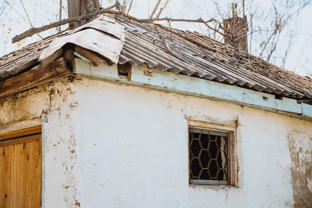 住宅問題の修理を必要としている古い荒廃した天候に打たれた家