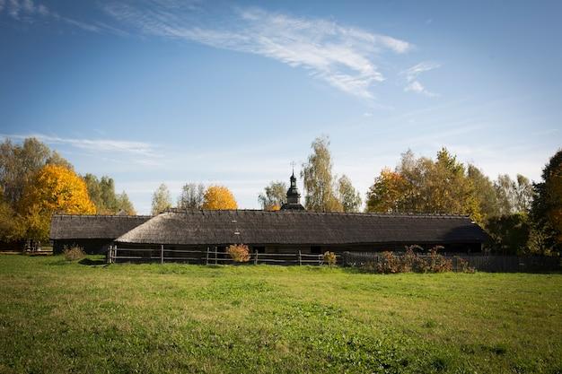 Старая деревенская деревянная хижина. на заднем плане - деревенская деревянная церковь. фото высокого качества