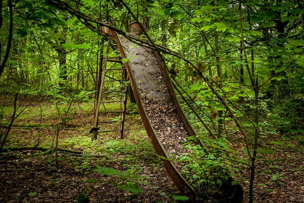 チェルノブイリ市の緑の森の真ん中に立っている古いさびた子供たちの滑り台