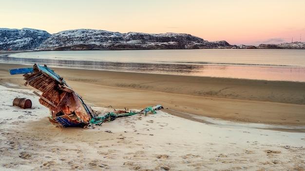 海岸の嵐で捨てられた古いさびた漁船。船の墓場、バレンツ海の海岸にある古い漁村、コラ半島、テリベルカ、ロシア。