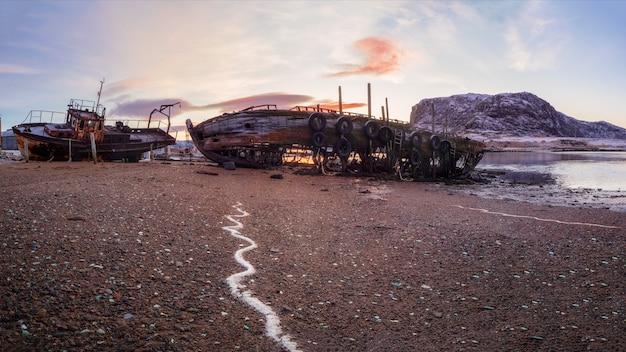 Старая ржавая рыбацкая лодка, брошенная штормом на берегу. кладбище кораблей, старая рыбацкая деревня на берегу баренцева моря, кольский полуостров, териберка, россия.