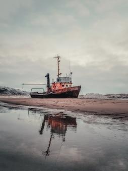 バレンツ海の砂浜に打ち上げられた古いさびた漁船。本物の北海。チェベルカ。
