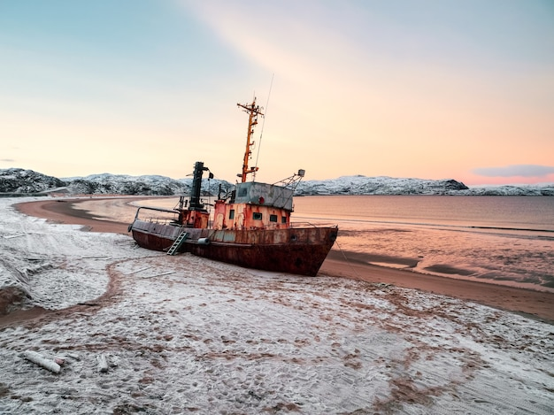 バレンツ海の砂浜に打ち上げられた古いさびた漁船。本物の北海。
