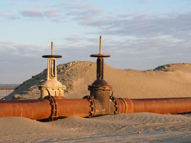 バルブ付きの砂漠の古いさびた石油パイプライン。夜明けの石油またはガスのパイプライン。天然資源の採掘。