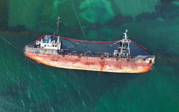 古いさびたタンカーが海に横たわっています