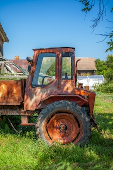 Возле сарая стоит старый ржавый трактор. красный старый трактор для хозяйственных нужд и уборки стоит на зеленой траве.