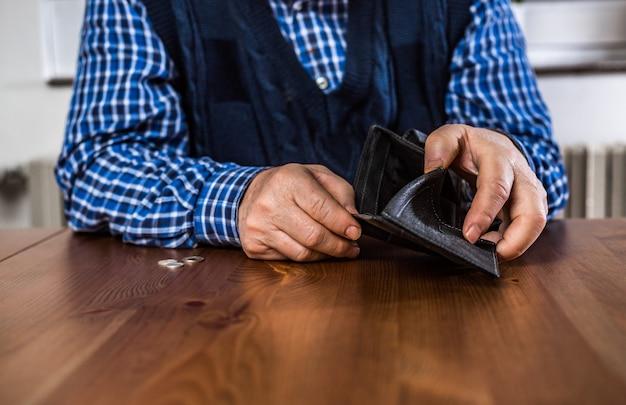 Пожилой пожилой мужчина показывает пустой кошелек без денег во время covid-19, пандемии коронавируса, экономического кризиса