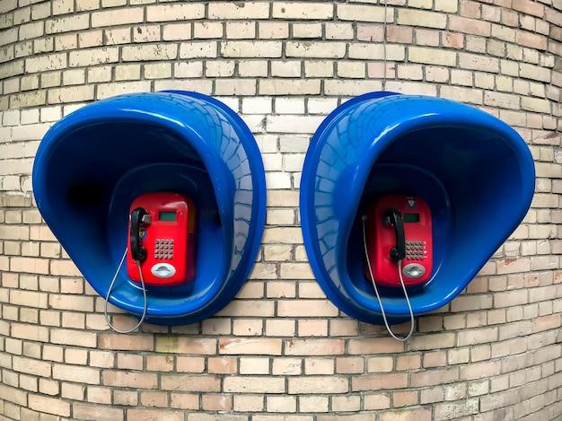 흰색 벽돌 벽에 오래된 소련 도시 전화 상자