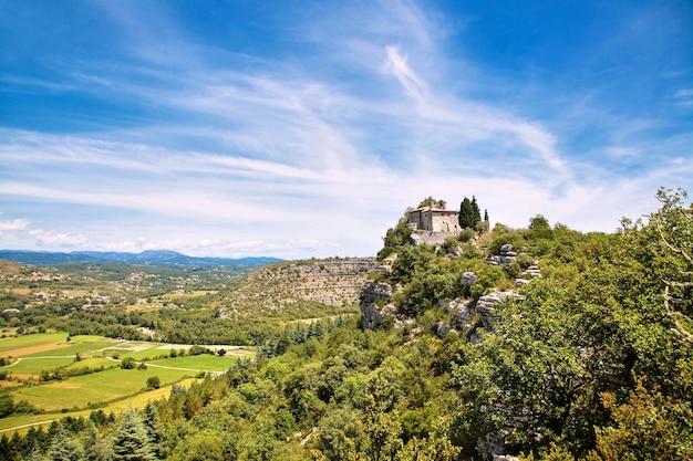 岩の端に立っている古い石造りのチャペル、教会または修道院。山から川の谷までの美しい景色。フィールド、牧草地、道路、白いふわふわの雲、青い空。