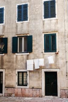 木製の窓とリネンがロープで乾かされた古い石の壁。旧市街の背景