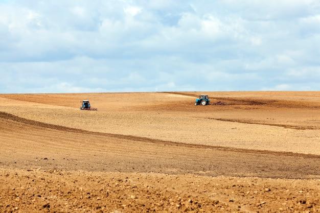오래된 트랙터는 파종을 위해 밭을 준비하는 동안 밭에서 토양을 쟁기질합니다.