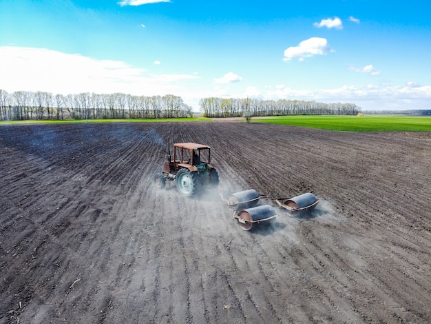 作物を播種するためにトレーラー式ローラーブレードを運ぶ古いトラクター。機械の空気から発生する干ばつやほこり。