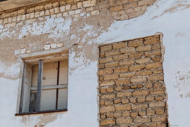 板張りの窓とレンガを敷いた廃墟の崩れかけた家の古い壁