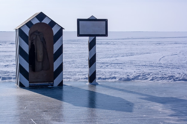 На границе льда и снега стоит старая сторожевая башня и столб с местом для надписи. наклонные черные полосы на рубке и столбе. по горизонтали.