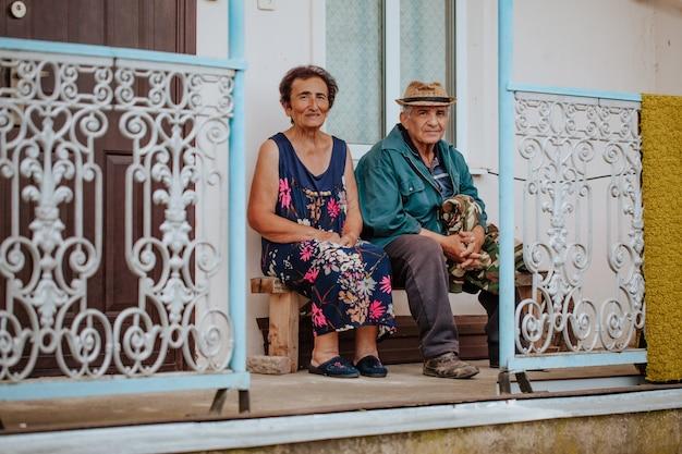 老婆と帽子をかぶった老人は錬鉄製の手すりでポーチに座っています