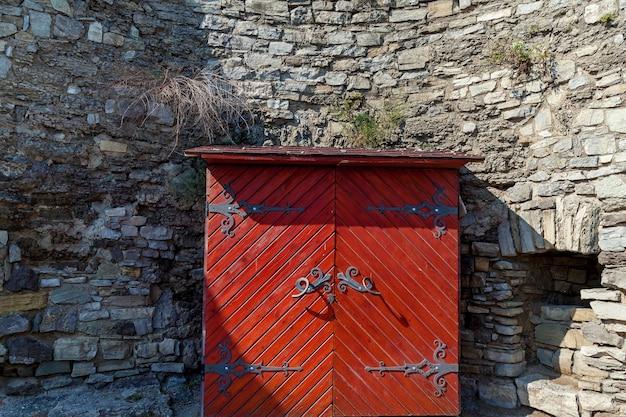 カミアネツィ・ポディルスキー城の灰色の壁の背景に鍛造された要素を持つ古い木製の食器棚。
