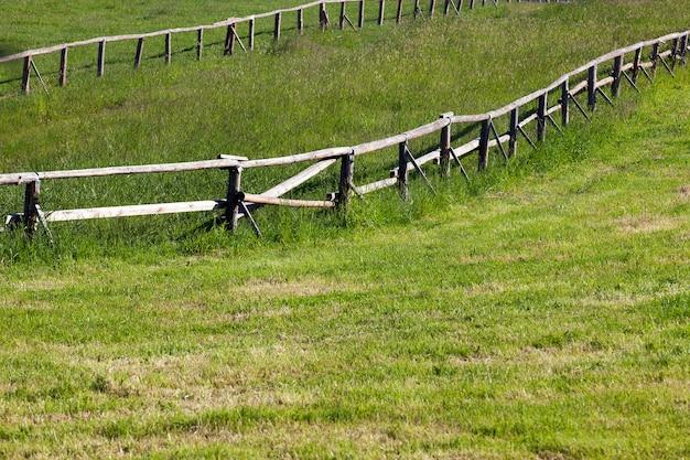 Старый деревянный забор для животных, выращенных на ферме.