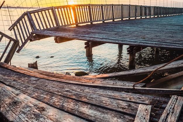 오래된 나무 산책로는 시간이 지남에 따라 판자가 부서지고 마모된 호수로 이어집니다.