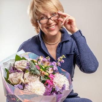 花の美しい花束を保持しながら、年上のブロンドは笑っています。ママの誕生日