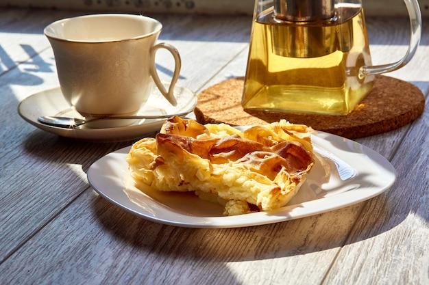 木製のテーブルの上の皿のオムレツティーポットとマグカップ