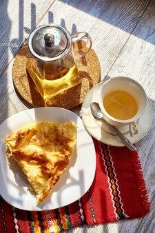 Омлет в тарелке на деревянном столе чайник и кружка