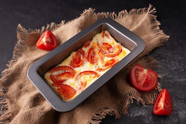 Омлет из яиц и помидоров на прямоугольной сковороде на холсте из ткани темное фото
