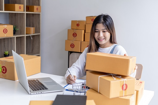 オンライン販売者は、顧客への配送に備えて小包ボックスの数を数えています。茶色の小包ボックスは、損傷を避けるためにロープで結ばれています。オンラインショッピングのコンセプト。