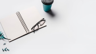 An open blank spiral notebook with eyeglasses; disposable coffee cup and push pins on white background