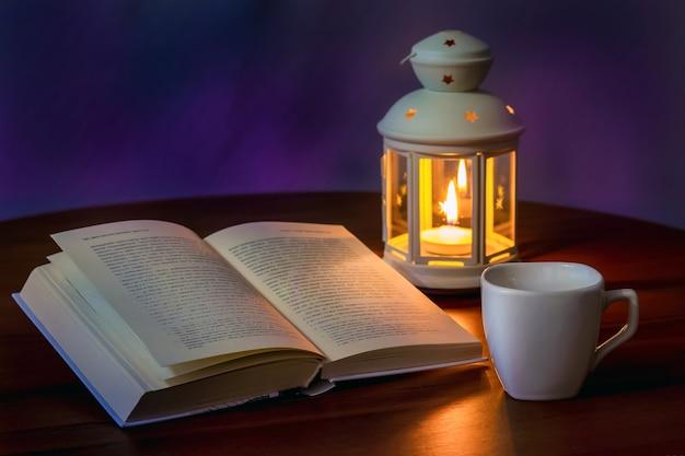 開いた本と夕方にキャンドルとランタンの光の中でお茶やコーヒー