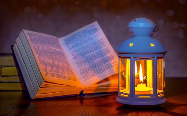 提灯の明かりで照らされた開いた本。開いた本の近くのキャンドルとランタン。ろうそくの明かりで読書。ロマンチックな夜