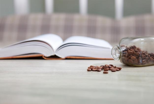 Открытая книга на белом столе и бутылка кофейных зерен