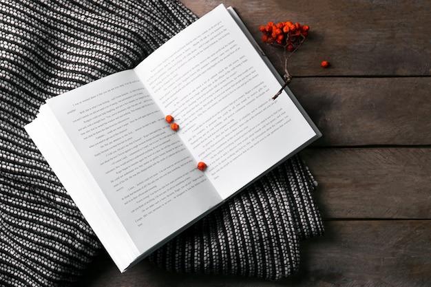열린 책 마가목 열매와 나무 테이블에 담요